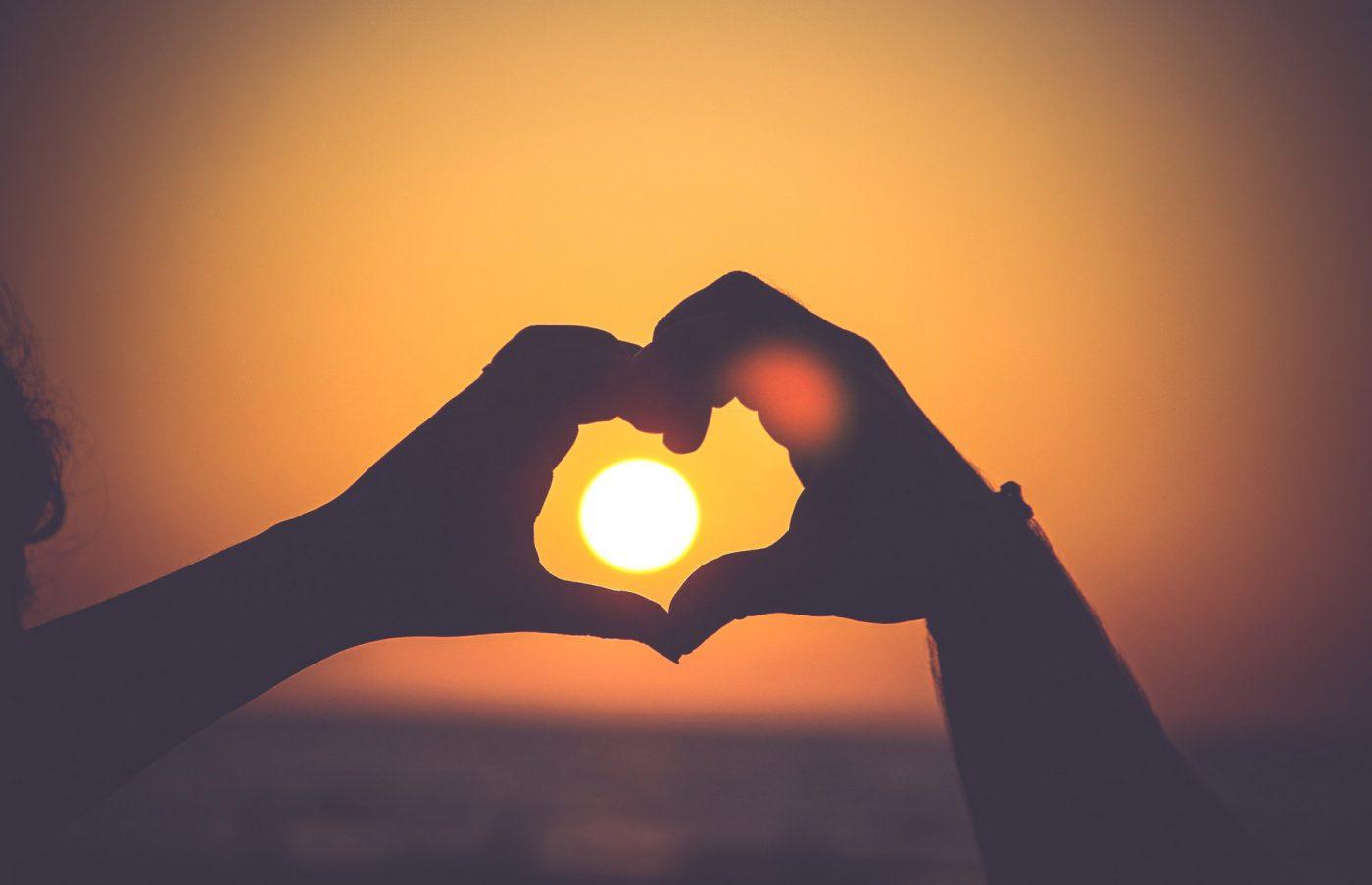 Zwei Hände vor einem Sonnenuntergang zu einem Herz geformt.