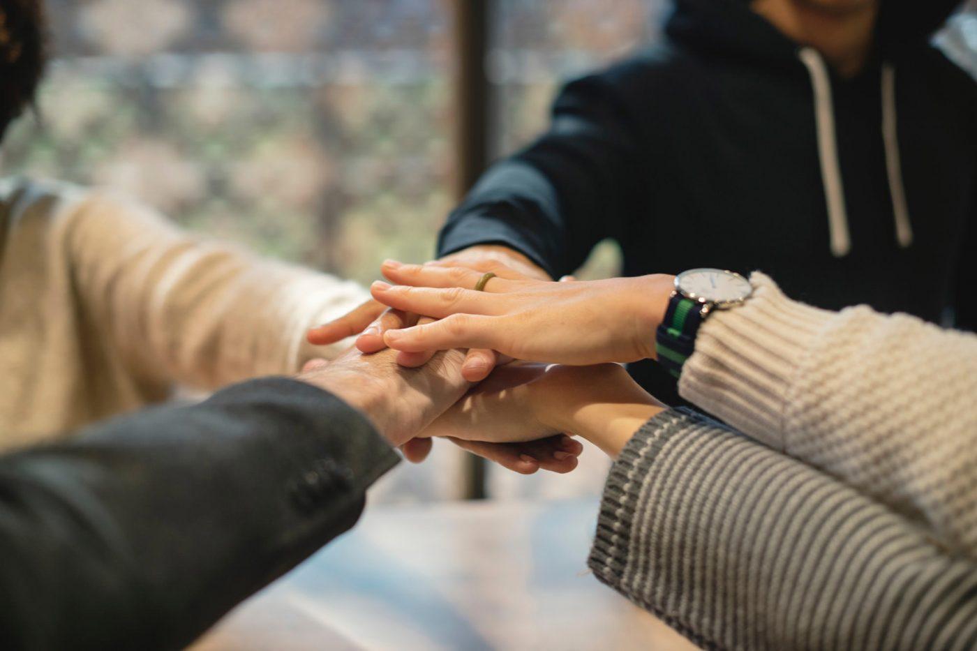 Aufeinandergehaltene Hände einer Gruppe von Menschen