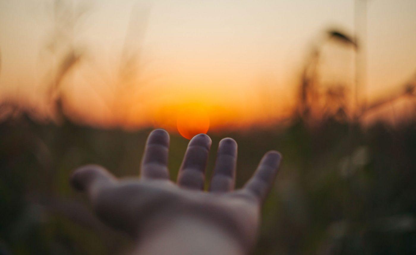 Ausgestreckte Hand in der Ich-Perspektive an einem Feld bei Sonnenuntergang