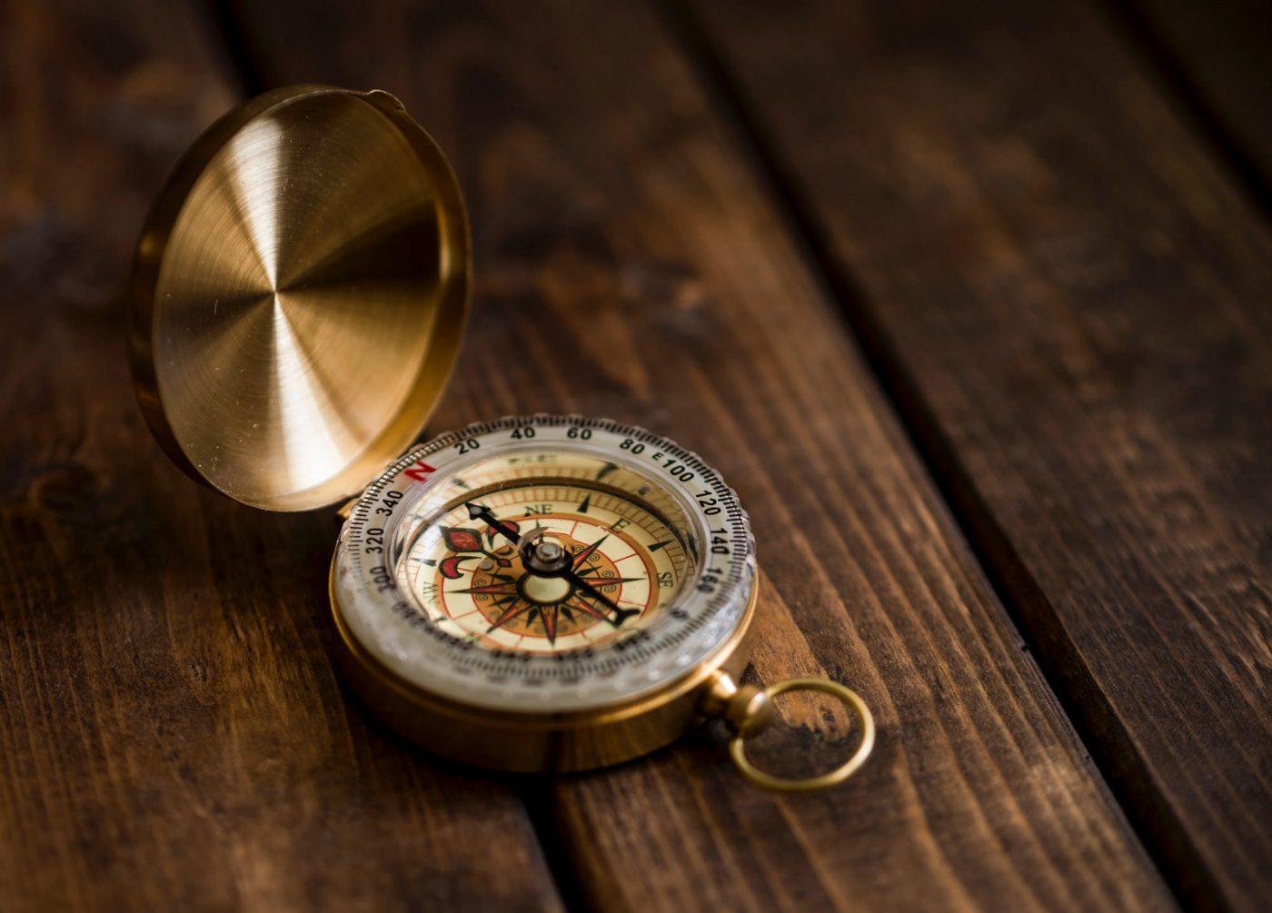 Ein Kompass in goldenem Gehäuse auf einem dunklen Holztisch.
